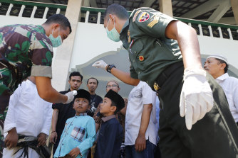 Military officials check the body temperature of a boy before prayers at a mosque in Bali, Indonesia last Friday.