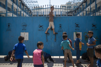 Palestinian schoolboys try to look from the door of a United Nations-run primary school at damage caused by an explosion, in Gaza City.