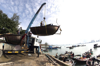People move fishing boats to a safer place ahead of the arrival of typhoon Molave in Danang, Vietnam.