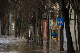 A man walks through floodwater following a storm in Girona, Spain.