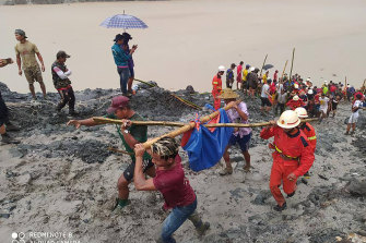 Rescuers carry a recovered body of a victim in a landslide from a jade mining area in Hpakant, Kachine state, northern Myanmar.
