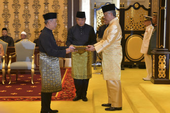 Muhyiddin Yassin, left, is sworn in by King Sultan Abdullah Sultan Ahmad Shah at the National Palace in Kuala Lumpur.