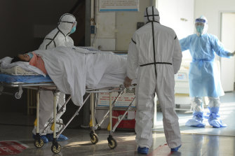 Medical workers in protective suits move a coronavirus patient into an isolation ward at the Second People's Hospital in Fuyang in central China's Anhui Province.