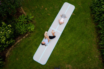 Ella and Scarlett Chappell playing on their new inflatable gymnastics mat.