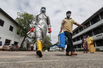 Members of Sri Lanka's St John's Ambulance disinfect a school in Colombo.