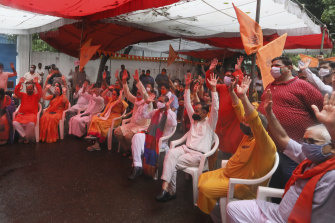 Hindus shout religious slogans as they watch a live telecast on a giant screen the groundbreaking ceremony.