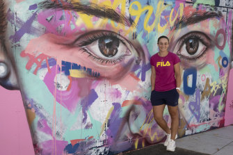 Ashleigh Barty in front of the mural of her at Melbourne Park.