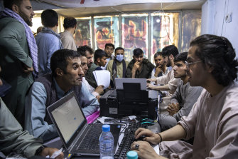 Afghans crowd into the Herat Kabul internet cafe to apply for visas.