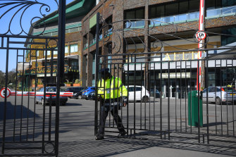 A security guard shuts the gates of The All England Tennis and Croquet Club on Wednesday.