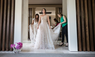 Aphrodite Spiropoulos (centre) tries on a rental gown by Klovia Couture's Sylvia Ktori (left) and Kony Diaman.