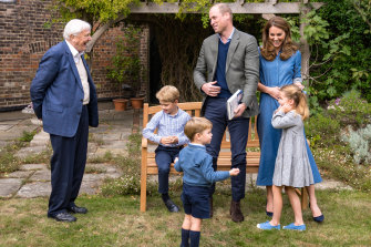 Prince William, Catherine, Duchess of Cambridge, Prince George (seated), Princess Charlotte and Prince Louis meet with Sir David Attenborough in the gardens of Kensington Palace, in this picture released by the royal family.