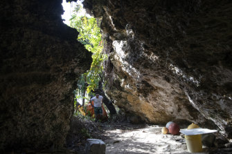 Conservationist Brett Howell drags a sackful of plastic into one the island's limestone caves.
