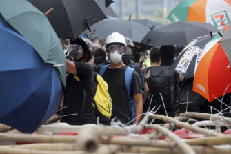 A protester stands at a barricade made of bamboo poles in Hong Kong on Saturday. Pro-democracy protesters took to the streets calling for the removal of lamp posts that raised fears of increased surveillance.