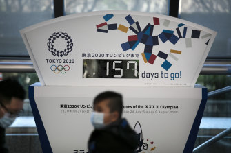 Coronavirus fears: People wear face masks in Tokyo as the countdown clock to the Olympic Games ticks down.