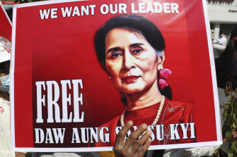 A protester holds a sign demanding Myanmar's elected civilian leader Aung San Suu Kyi be freed.
