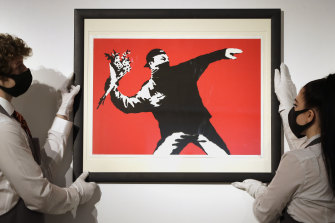 Gallery technicians display a Banksy called Love is in the Air