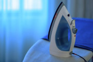 M5YD28 closeup of a household hand iron resting in upright position in home bedroom iron letters traveller
