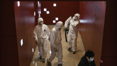 Workers wear protective suits in a mall in Beijing, China.