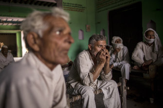 People discuss how to handle the pandemic in the village of Basi, Uttar Pradesh, India.