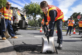 Minister Jaala Pulford helps out with road repairs last year.