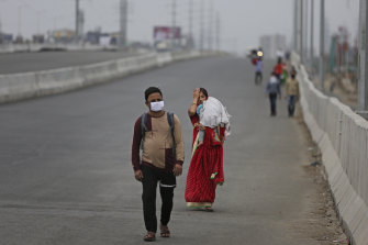 An Indian couple carrying an infant walk along an expressway hoping to reach their home, hundreds of kilometres away, as the city comes under lockdown in Ghaziabad, on the outskirts of Delhi.