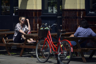 Two women sit outside a closed pub in London as Britain faces its seventh week of coronavirus lockdown.