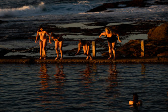 After viewing the sunrise,  a group of swimmers dive into Mahon Pool at Maroubra, on the last day of winter, in Sydney.