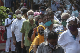 People queue in Mumbai, India, on Monday to receive their COVID-19 vaccine.