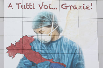 A mural on the side of a building in Lombardy thanks medical workers.