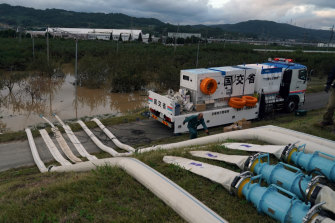 Water pumps drain flooding from a breached levee in Naganuma, near the city of Nagano in Japan.