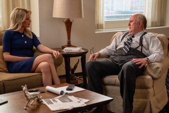 Charlize Theron as Megyn Kelly and John Lithgow as Roger Ailes in Bombshell.
