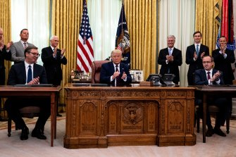 US President Donald Trump, centre, Serbia President Aleksandar Vucic, left, and Kosovo's PM Avdullah Hoti applaud following the signing ceremony in the Oval Office.