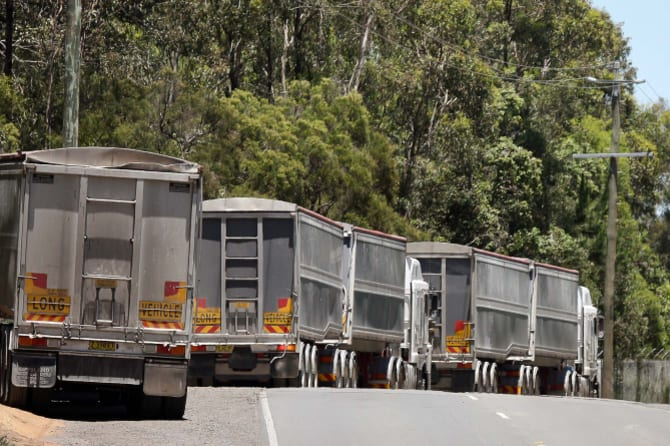 The queue: Trucks with NSW licence plates carrying construction waste line up outside Cleanaway's Willawong recycling facility on Brisbane's southside.