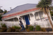 Dunedin, New Zealand - January 14, 2013: An Asian couple walk past a house on Baldwin Street, the steepest street in the world. Image has been intentionally rotated. iStock image for Traveller. Re-use permitted. World's steepest street