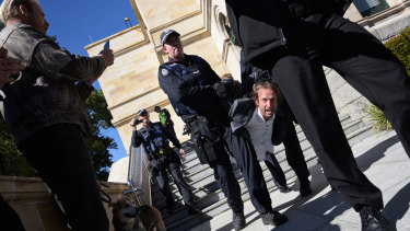 A man arrested by WA police is carried down the steps at Parliament House.
