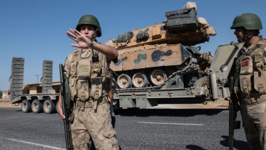 Turkish military vehicles carry tanks to the Syrian border on October 12, 2019.