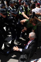 Police intervene to protect Shaun Islip, lying on the ground, from protesters outside the Melbourne Exhibition and Convention Centre during the climate protests on October 29.