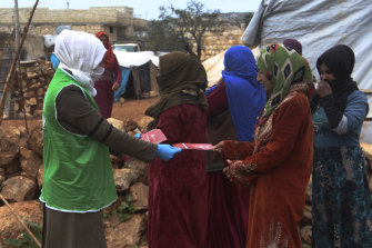 An aid worker with the Turkish humanitarian group IHH distributes  instructions on how to avoid coronavirus infection to Syrian women at a camp for internally displaced persons in northern Syria.