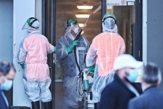 Cleaners disinfect the lower floor of an apartment building in Blacktown on Tuesday.