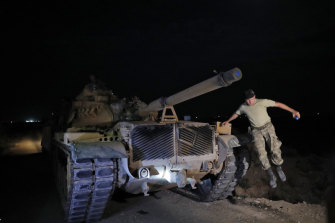A Turkish army officer jumps from his tank on the Turkish side of the Syrian border as forces reposition ahead of a move into Syria.