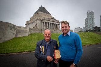 Thank you: Clark Pettigrew, right, hands the World War I diary of Morris Milliken to Morris's nephew, Malcom Milliken at Melbourne's Shrine of Remembrance.