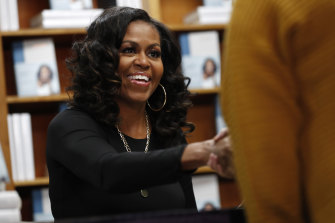 Former first lady Michelle Obama greets readers as they buy signed copies of her memoir, Becoming.