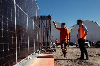 5B staffer Victor Rego (left) shows new head of product development Lloyd Niccol a set of the firm's pre-fabricated solar modules in Kurnell, Sydney.