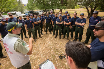 Firefighters from America being briefed by deputy incident controller Jarrod Hayse at the incident control centre near Myrtleford on Friday.