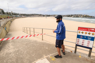 A ranger tapes off an entrance to Bondi Beach on Saturday afternoon.