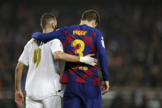 Real Madrid's Karim Benzema (left) and Barcelona's Gerard Pique walk off the pitch together after the draw.