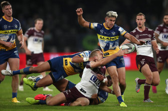 Tom Trbojevic of the Sea Eagles attempts to pass around Dylan Brown.