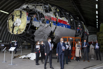 Presiding judge Hendrik Steenhuis, centre, and other trial judges and lawyers view the reconstructed wreckage of Malaysia Airlines Flight MH17.
