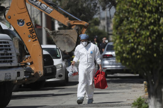 A forensic investigator carries equipment outside the house where police found bones under the floor in the Atizapan municipality of the State of Mexico.