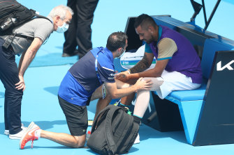 A physiotherapist assess Nick Kyrgios' knee during a break in his match against Borna Coric of Croatia at Melbourne Park.